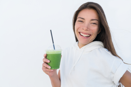 Happy Asian woman drinking healthy green spinach smoothie cup detox for weight loss diet. Young smiling fitness sporty girl with vegetable juice drink from juicing bar health trend, white background. Фото со стока