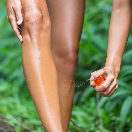 Woman spraying mosquito repellent on leg skin. Woman using Insect repellent bug spray bottle on legs, body and clothing outdoor in nature forest. Prevention for zika virus affecting tropical areas.