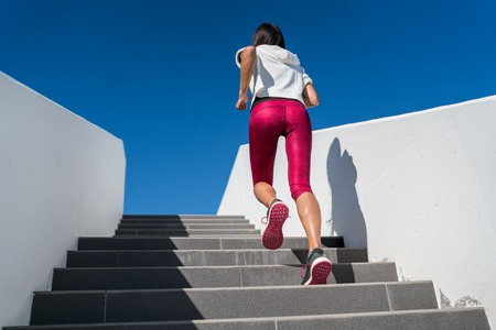 Stairs climbing running woman doing run up steps on staircase. Female runner athlete going up stairs in urban city doing cardio sport workout run outside during summer. Activewear leggings and shoes. Stock Photo