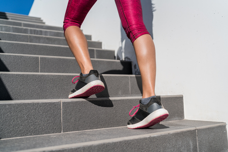 Stairs climbing running woman doing run up steps on staircase. Female runner athlete going up stairs in urban city doing cardio sport workout run outside during summer. Activewear leggings and shoes. Imagens