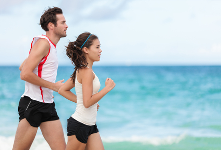 Fitness interracial couple runners running on beach. Running couple jogging together outside on ocean background. Athletes training cardio outdoors working out. Stock Photo