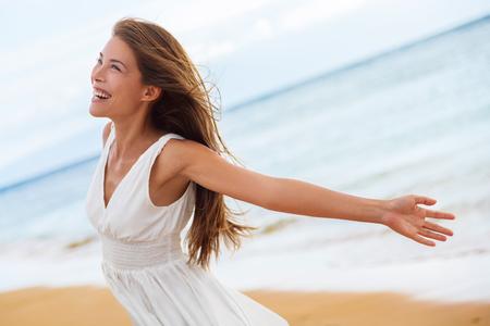 자연을 즐기는 해변에서 무료 행복 한 여자. 자연 아름다움 여자 자유 즐거움 개념에 야외. 혼합 된 레이스 백인 아시아 소녀 여행 휴가 방학 드레스에