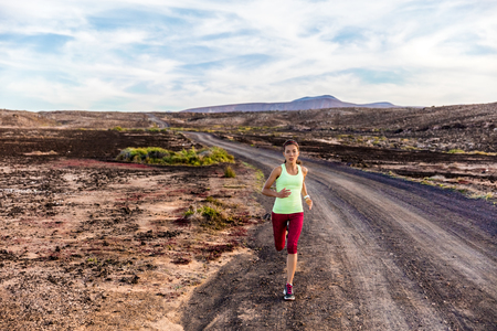 Athlete runner running on nature mountains trail. Asian sports woman training intense cardio workout jogging working out on amazing summer volcanic rocks desert landscape outdoors. Determination.