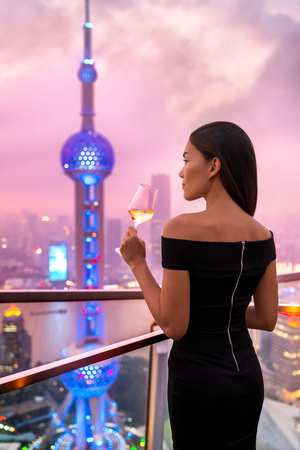 Elegant asian woman in gown drinking white wine glass at rooftop bar terrace looking at city lights skyline view of Shanghai in sunset. Luxury travel or high end lifestyle. Stock Photo