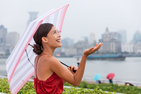 Rain, weather concept - happy Asian tourist woman under umbrella holding hand up checking the amount of raindrops during city walk on Shanghai waterfront harbour. Young chinese businesswoman. Banque d'images