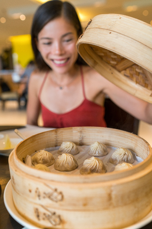 Asian woman eating typical shanghai chinese food xiao long bao soup filled dumplings at restaurant. Asian girl opening bamboo steaming tray with hot fresh traditional handmade pork buns. Stock Photo