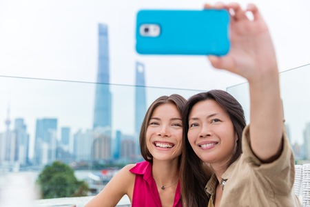 Chinese mother and daughter taking selfie together. Happy multiracial family on travel holiday in Shanghai, China. Mom holding mobile phone on outdoor cafe terrace with view of the Bund and Pudong.