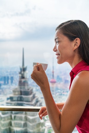 Asian woman enjoying afternoon high tea in luxury cafe or fancy restaurant with city view of Shanghais landmark skyscrapers in Pudong, China. Chinese tourist lady drinking hot cup of coffee relaxing.