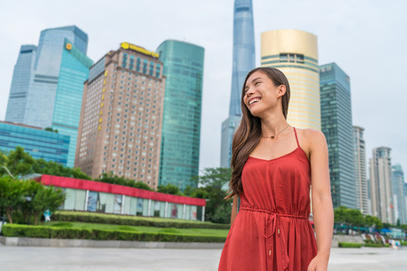 Shanghai woman walking in Pudong by huangpu river with view of the business district. Tourist or casual girl in beautiful red dress enjoying walk at Pudong boardwalk. Stock Photo