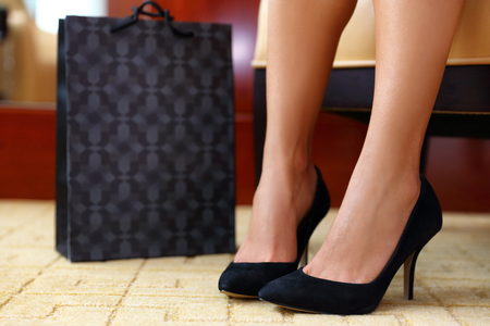 Woman buying new shoes. Closeup female feet wearing black suede high heels next to shopping bag, girl trying on her new fashion sexy footwear. At home or store. Banque d'images
