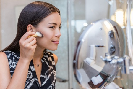 Asian woman putting makeup in home bathroom using a contour brush to apply bronzer powder under cheek bones, then blend it upwards onto cheeks. Morning routine in make-up mirror. Banco de Imagens