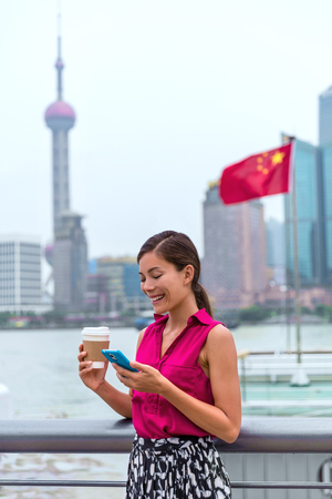 Business woman in Shanghai using smart phone app drinking coffee in Pudong financial district. Professional businesswoman on China travel on the Bund waterfront with Chinese flag in background Banque d'images