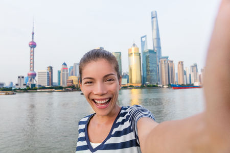 Happy Asian tourist woman taking selfie on The Bund. Smiling young lady holding smartphone camera to take a picture of herself in front of Shanghais landmak, skyline of skycrapers in Pudong, China. Banque d'images