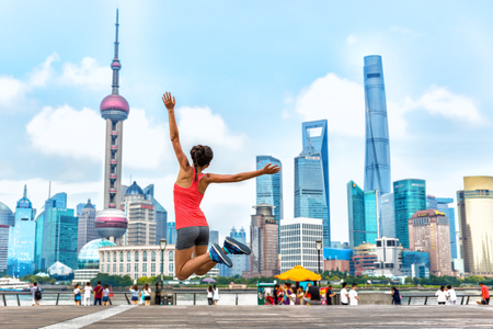 City success urban woman jumping of joy in Shanghai skyline background. Happiness, happy runner. Weight loss winning challenge concept.
