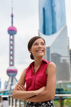 Happy business woman portrait in Shanghai, China showing Pudong financial district and tower. Proud confident young successful corporate executive or professional Asian multiracial businesswoman.