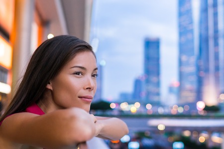 Urban city girl thoughtful and alone looking at city lights at night in Pudong, Shanghai, China. Multicultural Asian Chinese  Caucasian young woman professional enjoying time in financial district. Stock Photo