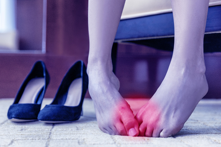 Medical concept. Foot pain. Body health problem, healthy feet swollen joints or blisters, wounds on skin. Painful barefoot woman at home or office with high heels in the background 스톡 콘텐츠