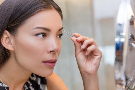 Asian woman plucking eyebrows with tweezers using eyebrow tweezer at home in bathroom makeup mirror. Closeup of a girls face while she is removing her facial hairs. Eyebrows beauty care.