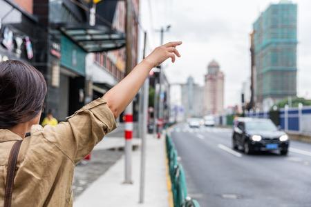 도로에서 rideshare 검은 차를 타고. 아시아여자가 손으로 상해 거리, 중국 승객에 대 한 전화 응용 기술을 사용 하여 온라인으로 타기를 요청하는 택시를