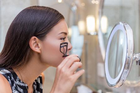 Vrouw die wimperskrulspeld krullende wimpers gebruiken vóór mascara in aangestoken ronde make-upspiegel van luxehotel of huisbadkamers. Mooi Aziatisch meisje die klaar in de ochtend worden die bezinning bekijken.