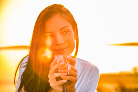 Morning coffee happy woman drinking hot drink enjoying first cup of the day on outdoor balcony in sunrise sunshine glow. Asian girl home comfort lifestyle. Banque d'images