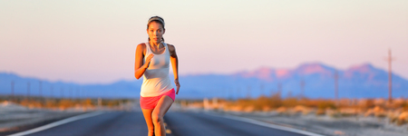 Athlete running on desert sunset road working out cardio training. Asian woman runner athlete sprinting.