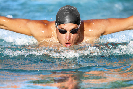 adentro y afuera: Swimmer. Man swimming butterfly strokes in pool competition. Competitive male sport athlete swimmer wearing swimming goggles and cap. Young caucasian fitness model face portrait.