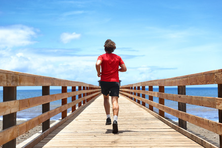 Running runner sport man jogging on beach boardwalk living active lifestyle. Workout outside person with fit body training for weight loss success, man taking step towards life happiness.