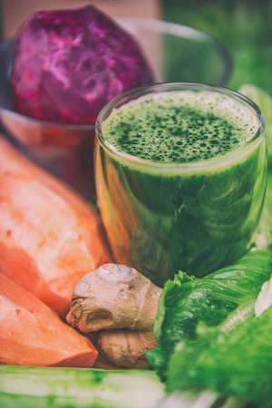 Green vegetable juice smoothie with root vegetables such as beets, sweet potato and ginger, and lettuce. Spinach, cucumber, leafy greens ingredients for vegetarian smoothies. Stock Photo