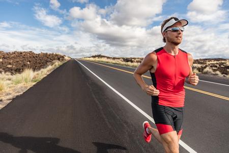 Geeigneter Athletenmann des Läufers, der in Triathlonanzugtraining für Eisenmann auf Hawaii läuft. Geeigneter männlicher Triathlet, der die Ausdauer cardio auf Straße ausübt. Standard-Bild