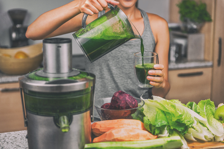 Mulher que juicing a fatura do suco verde com a máquina do suco na cozinha home. Dieta vegan de desintoxicação saudável com extrator vegetal prensado a frio para extrair nutrientes para a bebida smoothie. Foto de archivo - 87267892