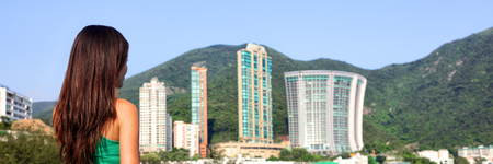 Real estate apartment condo buildings cityscape. Modern city landscape with skyscrapers towers in Hong Kong with business woman looking. Tourist girl travel, Repulse Bay beach, Hong Kong, China, Asia. Banque d'images