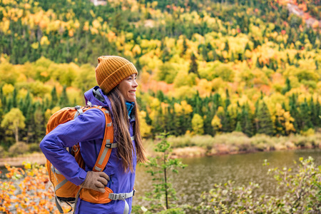 Autumn hiker girl outdoor in nature forest lake backpacking for camping travel trip. Happy Asian woman hiking outdoors with bag and hat, cold outerwear gear. Stock Photo