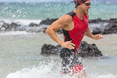 Triathlon-Schwimmenmann-triathlete Schwimmer, der aus Ozeanvollendenschwimmenkonkurrenz heraus läuft. Geeignete männliche Athletendschwimmen, die aus Ozean heraus mit dem Wasser spritzt, das Hintergrundtraining für ironman spritzt.