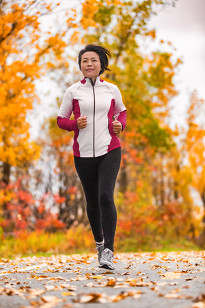 Autumn healthy middle aged mature woman in her fifties exercising cardio training for active lifestyle. Jogging Asian lady running outdoor in park. Banque d'images