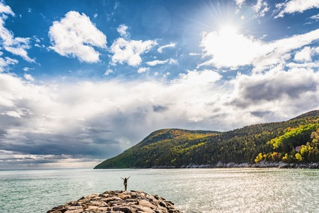 Autumn nature background canadian landscape in Quebec, Canada. Fall season St Lawrence river in Charlevoix region, North America. Tourist with arms up open in freedom happy of travel holidays.