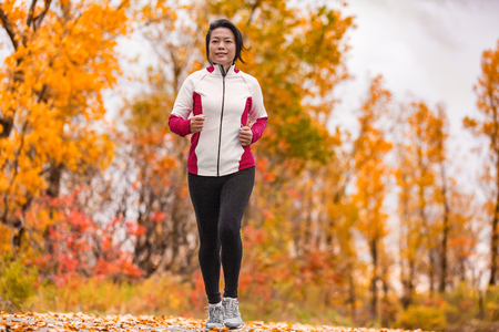 Middle aged mature Asian woman running healthy lifestyle Chinese lady jogging in fall park in her 50s. Middle age runner outdoor living in autumn city forest happy on weight loss fitness program. Banque d'images