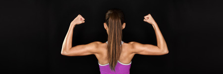 Strong fitness woman showing back and biceps muscles strength. Fit girl fitness model isolated on black background banner panoramic crop for copy space. Banque d'images