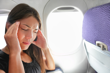 Travel plane sick woman. Fear of flying girl in airplane airsick with stress headache and motion sickness or airsickness. Person in airplane with aerophobia scared of flight frustrated sitting.