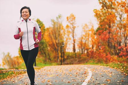 Rijpe Aziatische vrouw die actief in haar jaren '50 loopt. Midden oude vrouwelijke joggen buitenleven gezonde levensstijl in mooie herfst stadspark in kleurrijke herfst gebladerte. Aziatische Chinese volwassene in haar vijftiger jaren.