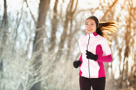 Winter run woman runner exercising in outdoor forest park. Asian athlete girl training cardio during cold season wearing gloves, warm headband for protecting the ears and jacket.