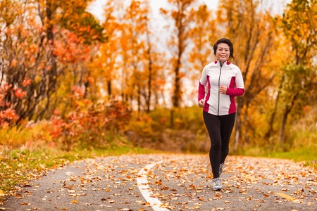 Middle age active and healthy Asian woman exercising weight loss body workout jogging running in park path autumn forest. Middle aged lifestyle. Lady in her 50s. Archivio Fotografico