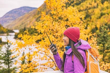 Autumn hiker camping woman talking on ham radio portable transceiver .Amateur radio operator woman speaking on handheld walkie-talking in mountains nature.