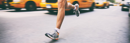 Runner athlete running in city street banner. Sport man training outside in urban background next to yellow cabs cars taxi in new york NYC. Stock Photo