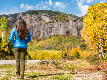 Autumn mountains travel tourist woman walking enjoying view of fall nature. Quebec tourism, tourist girl with forest outdoor background landscape on road trip.