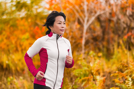 Active woman running and jogging. Middle aged Asian mature female jogger outdoor living healthy lifestyle in beautiful autumn city park in colorful fall foliage. Asian Chinese lady in her fifties. Archivio Fotografico