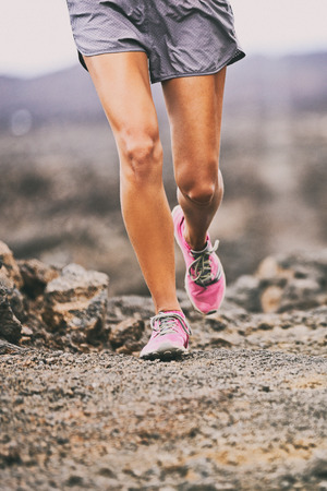 Running shoes sport exercise fitness woman athlete on trail run training on desert path outdoors. Lower body legs closeup hiking on hike nature. Stock Photo