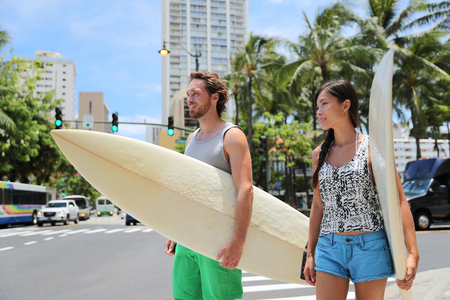 Honolulu Hawaii lifestyle surfers people walking in city with surfboards going to the beach surfing. Outside hawaiian surf living. Surfer couple crossing street. Waikiki, Honolulu, Oahu, Hawaii, USA. Фото со стока
