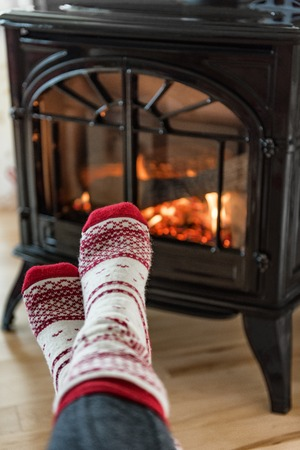Fireplace cozy winter woman warming up feet in wool socks by fire in after ski cabin house. Closeup or warm fire and cute legs during cold season.