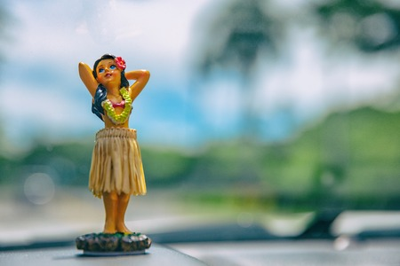 Hula dancer doll on Hawaii car road trip travel vacation. Aloha mini girl doll dancing on the dashboard in tropical nature landscape. Tourism and Hawaiian holiday freedom concept.